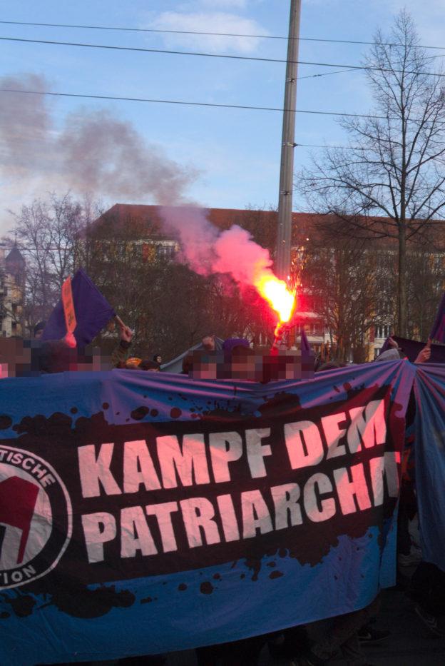 """Transparent mit der Aufschrift """"Kampf dem Patriarchat"""", dahinter ein Bengalo"""